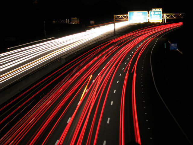 red and white trails formed by lights at night on the interstate