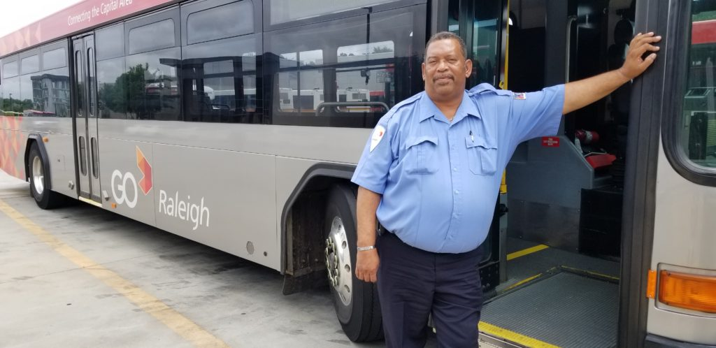 Bus driver Monroe Watson stands next to a GoRaleigh bus.
