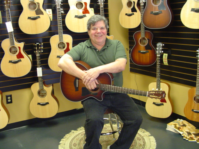 Harry Tuering sitting in his guitar shop